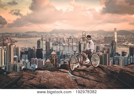 Man with bycicle up to the hill over the vetical city