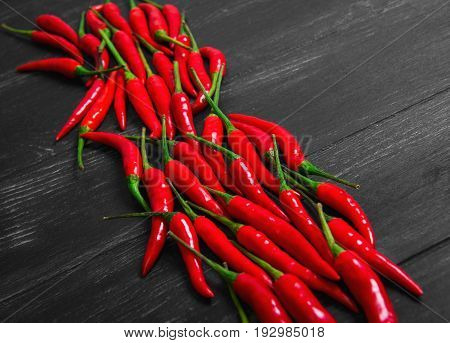 Red Hot Chili Peppers on darl black old wooden table Overhead view of chili pepper on wood background.