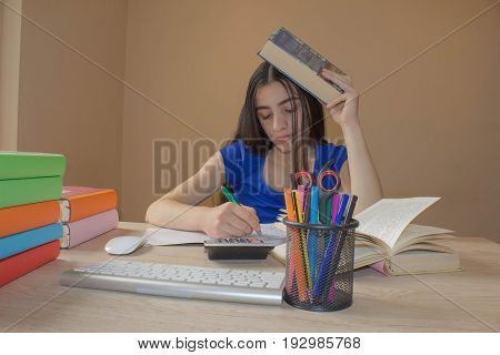 Open book hardback colorful books on wooden table. Young girl sitting at desk at home doing homework.education concept