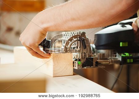 Man working with carving equipment in workshop. Electronic device cutting wooden bar closeup, worker carpenter at workplace cut planks made of wood
