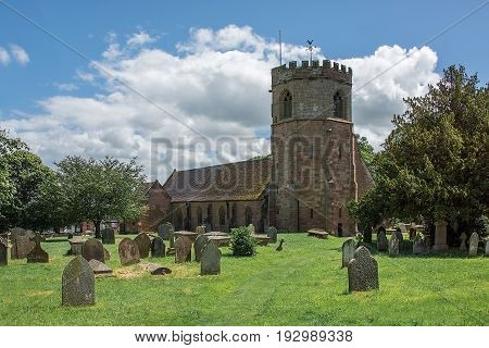 A horizontal image of a typical english country village church standing in a cemetery and taken on a sunny day with a blue sky