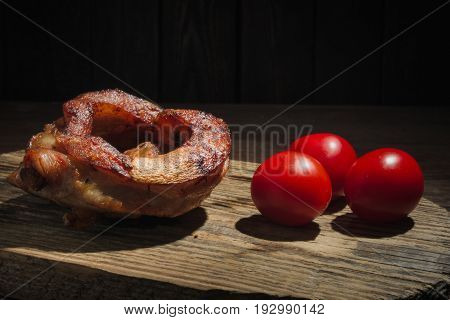Slice of roasted pork knuckle with cherry tomato on dark wooden background