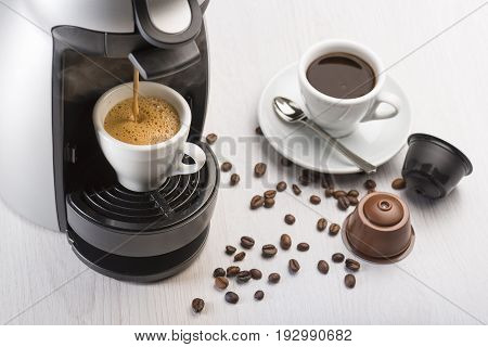 coffee machine in operation on table with coffee cup and coffee dispenser.