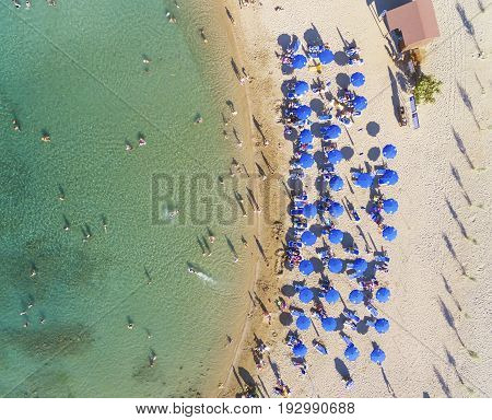 Aerial bird's eye view of sandy beach in Protaras Famagusta Cyprus island at the Agia Triada bay. Sun umbrellas sea beds and silhouette of people sunbathing and swimming during the summer holiday heat