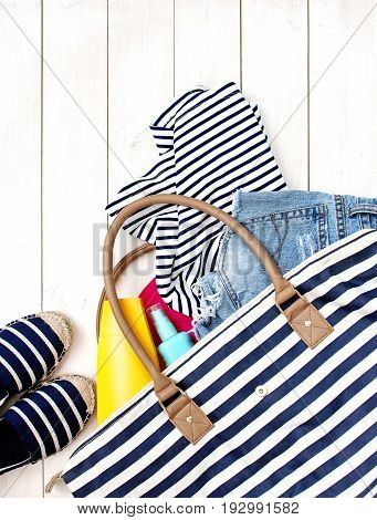 Beach women's clothes and a bag on a white background. Denim shorts summer shoes Striped T-shirt Sunscreen Top view White background