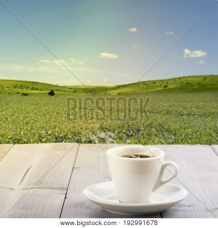 steamed cup of coffee on wooden table with sunny landscape on background.