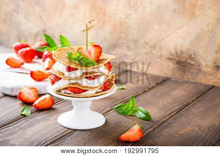 Pancakes mini cake with yogurt and strawberries on white porcelain cake stand. Children's party concept, copy space.