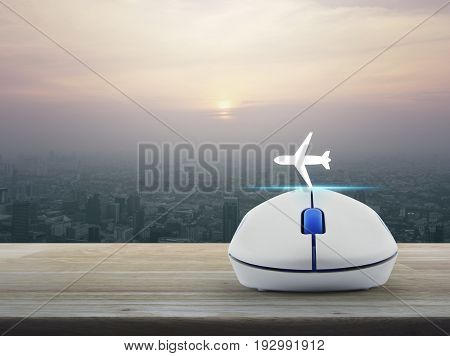 Airplane icon with wireless computer mouse on wooden table over modern city tower at sunset vintage style Business transportation concept