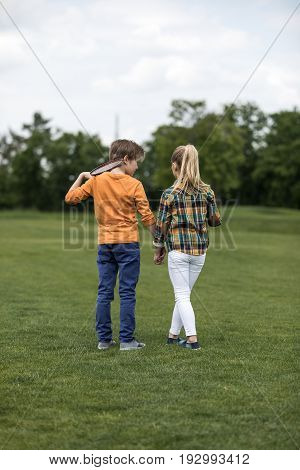 Rear View Boy And Girl Holding Hands While Standing On Green Field, Boy Holding Badminton Racquet On
