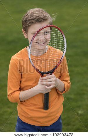 Adorable Smiling Little Boy Looking Through Badminton Racquet