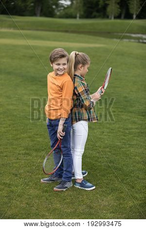 Adorable Boy And Girl Holding Badminton Racquets While Standing Back To Back On Green Grass
