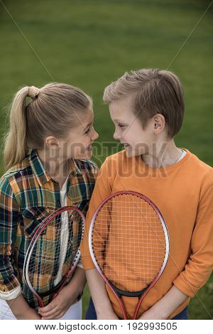 Cute Happy Siblings Holding Badminton Racquets And Smiling Each Other