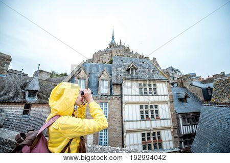 Young woman in yellow raincoat observing with binoculars beautiful buildings on the famous Mont Saint Michel island in France
