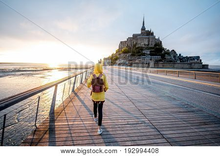 Young female traveler in yellow raincoat on the road to famous saint Michel island in France