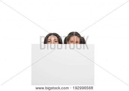 obscured view of mother and daughter hiding behind cube and looking at camera isolated on white
