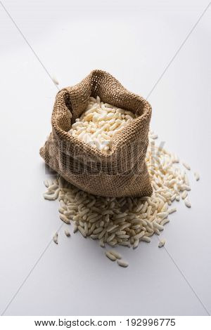 Puffed rice also known as Murmura or Murmure in hindi served in a colourful ceramic bowl or plate or over gunny bag, isolated, selective focus