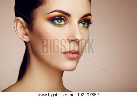 Portrait of beautiful young woman with rainbow make-up. Girl summer. Long eyelashes vivid colorful eyeshadows. Multicolored
