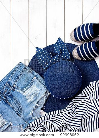 Beach women's clothing and accessories on a white background. Straw hat denim shorts summer shoes Striped jersey Top view White background