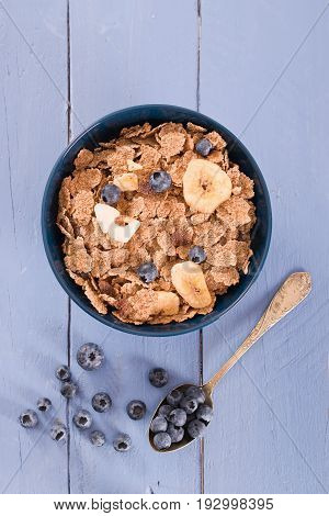 Breakfast with wholegrain cereals and blueberries on wooden table.