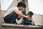 Behind the scene. Cameraman and assistant shooting the film scene with camera on outdoor location poster