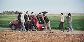Behind scene improvisation. Film crew team pushing car while cameraman from trunk of car shooting film scene with actor and actress on outdoor location. Group cinema set poster