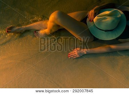 Sexy Asian Woman With Hat Lying Down On Sand Beach During Sunset. Woman Wear Black Swimsuit Relaxing