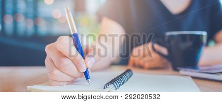 Business Woman Hand Is Writing On A Notepad With A Pen.