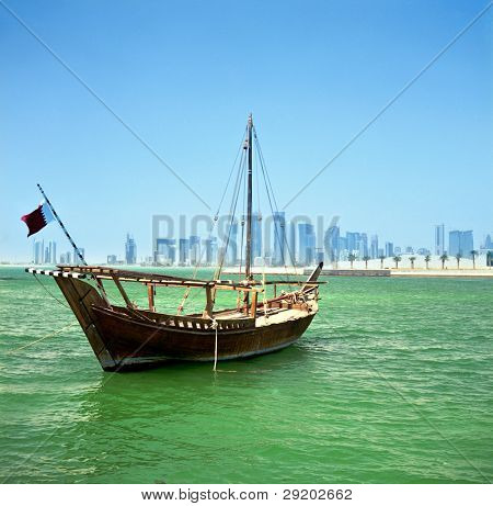 A traditional Arab dhow of the common Shuw'ai type moored in Doha Bay, Qatar, with the city's modern skyline in the background,