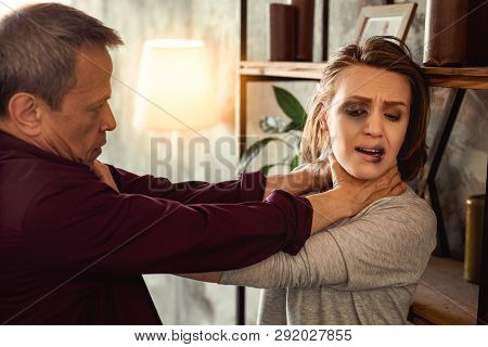 Resolute mad man choking his helpless woman with she leaning on shelves poster