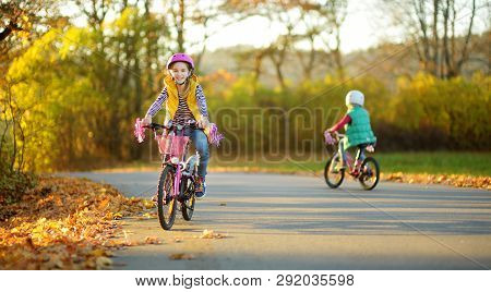 Cute Sisters Riding Bikes In A City Park On Sunny Autumn Day. Active Family Leisure With Kids. Child