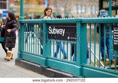 New York - March 16, 2015: People Entering New York Subway. Subway Sign On Green Steel Fence.