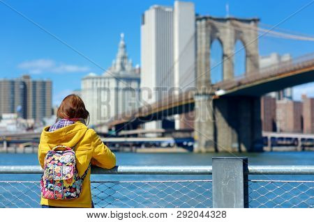 Happy Young Woman Tourist Sightseeing By Brooklyn Bridge, New York City, At Sunny Spring Day. Female