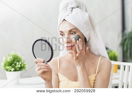 Face Skin Care. Attractive Young Woman Wrapped In Bath Towel, Applying Clay Mud Mask To Face. Skin C