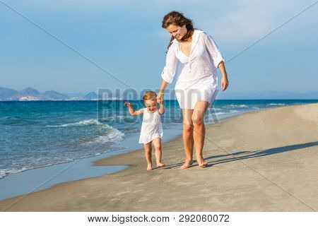 Mother and little daughter walking on the sea beach in Greece