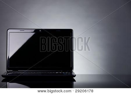 Laptop shot on reflective table on grey background