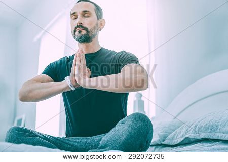 Inspired Relaxed Man Meditating In A Light Room