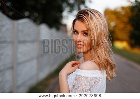 Pretty Happy Young Beautiful Blond Woman In An Elegant White Lace Blouse Posing Outdoors On A Sunny