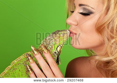 Portrait of a young woman with beautiful manicure kissing a iguana poster