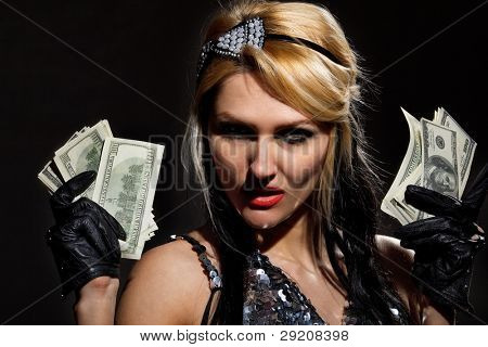 Sexy female with fan of dollars isolated in darkness poster