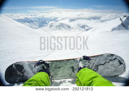 Point Of View Shot Of A Male Snowboarder Lying On The Snow