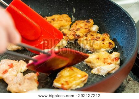 Round Chicken Cutlets Being Baked For Some Burgers For Wedding Meal On Pan With Blue Flames Under It
