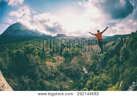 Highline In The Mountains. A Man Walks Along A Stretched Sling Against A Cloudy Sky. Highline Is On