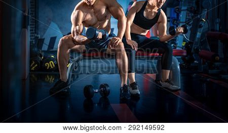 Bodybuilder Working Out With Dumbbell Weights At The Gym. Young Couple Is Working Out At Gym. Attrac