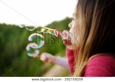 Cute Little Girl Blowing Soap Bubbles On A Sunset Outdoors On Beautiful Summer Day. Funny Activities