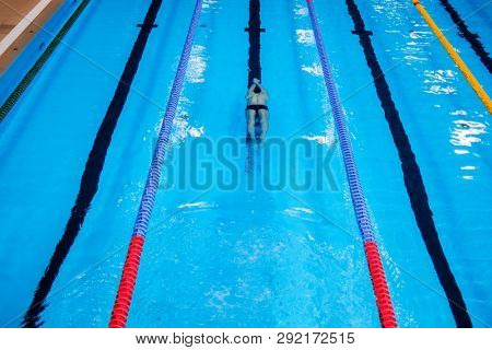 Muscular man under water in a swimming pool
