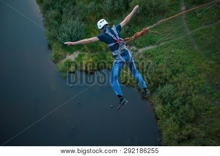 Extreme Jump From The Bridge. The Man Jumps Surprisingly Quickly In Bungee Jumping At Sky Park Explo