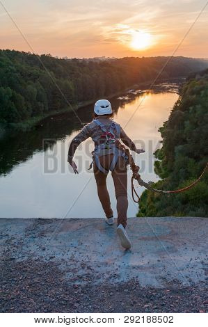 Girl Jumping From The Bridge. A Girl With An Incredible Time Is Engaged In Freestyle In Bungee Jumpi