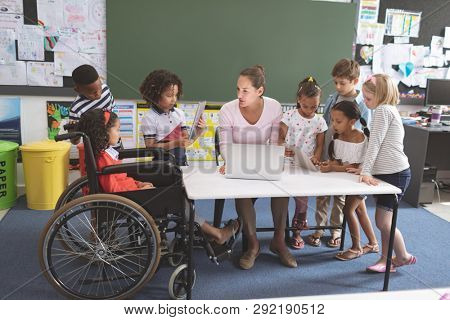 Students using digital tablet  while teacher interacting with students in classroom at school