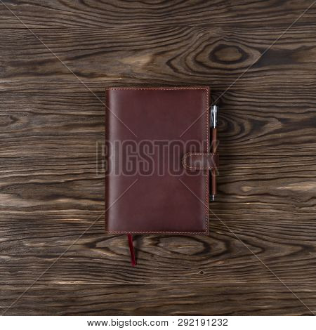 Brown Handmade Leather Notebook Cover With Notebook And Pen On Wooden Background. Stock Photo Of Lux