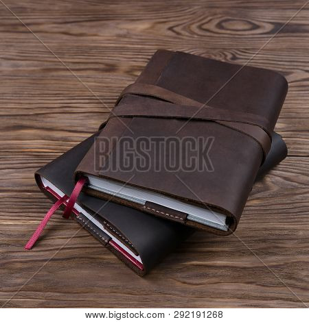 Brown And Black Handmade Leather Notebook Cover With Notebook Inside On Wooden Background. Stock Pho